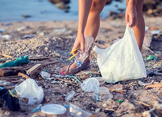 使い捨てプラスチック製品のゴミを拾う画像